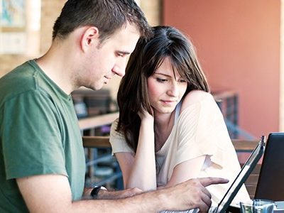 A man and woman on a laptop