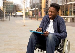 man writing in wheelchair