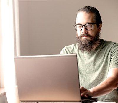 A man sitting at a desk near a window using a laptop
