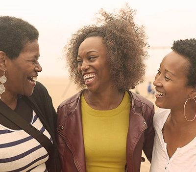 Three women smiling and laughing