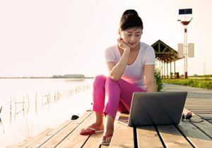 woman sitting on laptop outside by the water