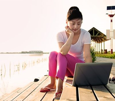 A woman using a laptop while sitting on a set of steps outside by the water