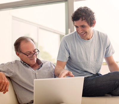 A father and son watching a video on a laptop