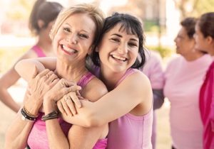 women hugging, wearing pink