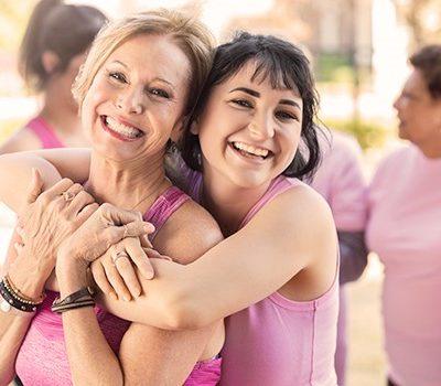 Women hugging, wearing pink