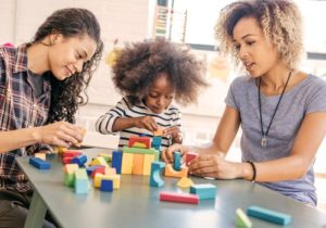 two women and a baby playing blocks