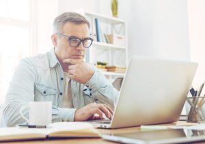 man sitting at desk on laptop