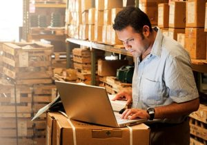 man in storage room looking at laptop