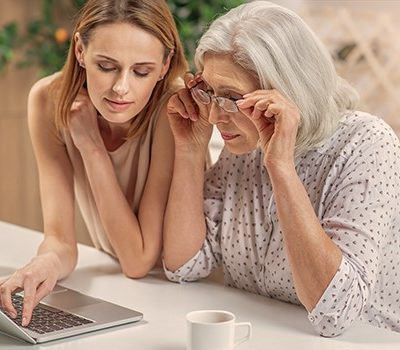 A elderly mother and her daughter sitting at a table and using a laptop