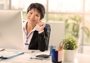 smiling woman sitting at desk