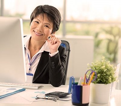 A woman smiling at the camera while sitting in front of her computer at her desk