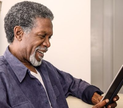 An older man reading from a tablet device