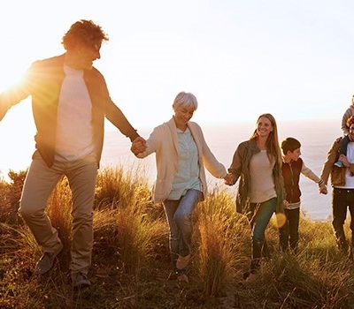 A family holding hands while hiking up a hill