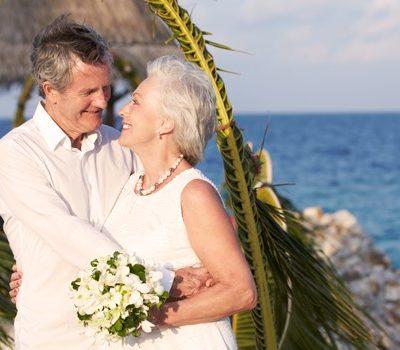 An elderly couple's wedding photo on a beach
