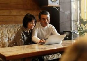 man and woman sitting at table, looking at laptop