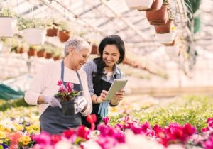 two women smiling and looking at flowers