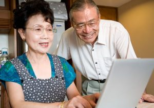 man and woman smiling, looking at laptop