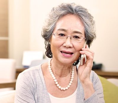 An elderly woman talking on a cellphone