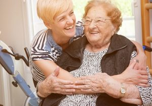 younger woman hugging elderly woman