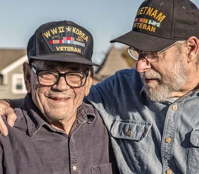 Two older men wearing veteran hats