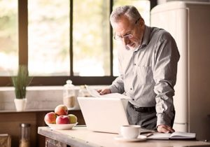 man reading on laptop in kitchen