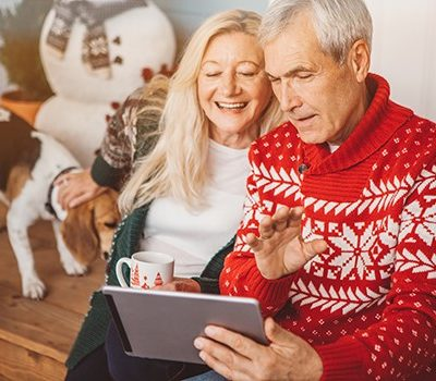 An older couple looking at a tablet device during Christmas