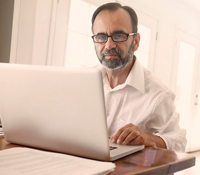 An older man sitting at a table while using a laptop