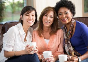 three women drinking coffee and smiling