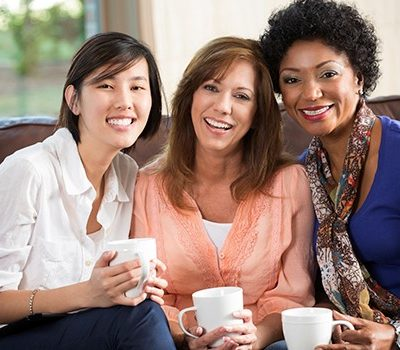 Three women smiling while holding coffee cups
