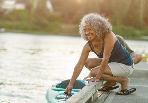 woman on dock getting into kayak