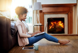 woman sitting by fireplace on her laptop