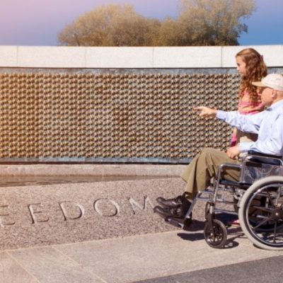 A man in wheel chair and woman looking at a war memorial
