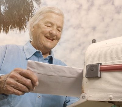 An older man mailing a letter