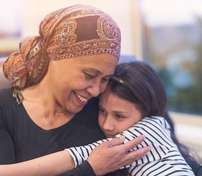 A woman hugging younger girl