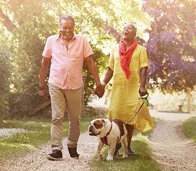 An older couple walking a dog