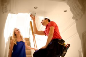 man and woman checking on smoke detector