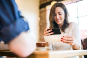 woman holding phone and smiling