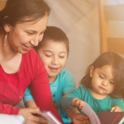 A mother and two children looking a books