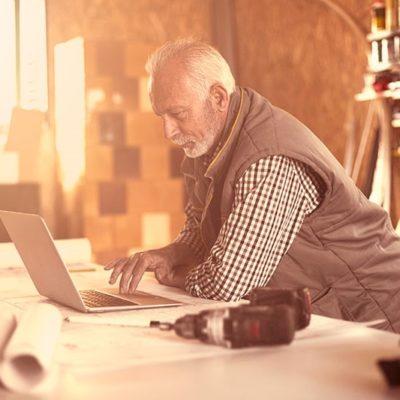 An older man using a laptop inside a workshop