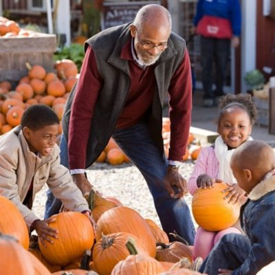 A grandfather and grandkids at a pumpkin patch