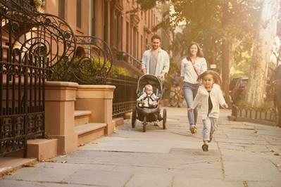 A family walking down a sidewalk in a city neighborhood