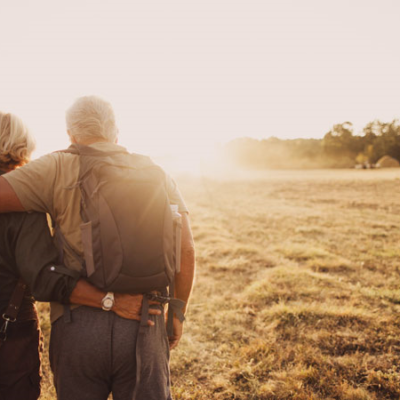 A older couple hiking through a field.