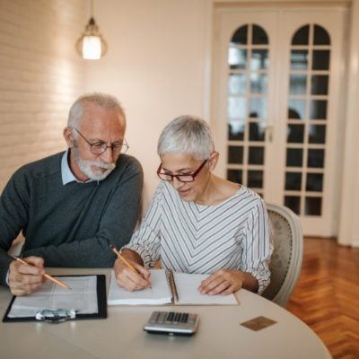 An elderly couple sitting at a table reviewing finances