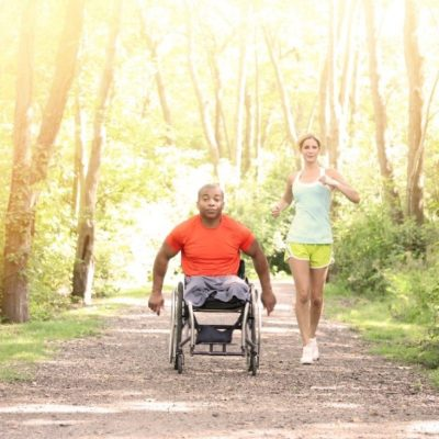 A man in a wheelchair accompanying a woman jogging