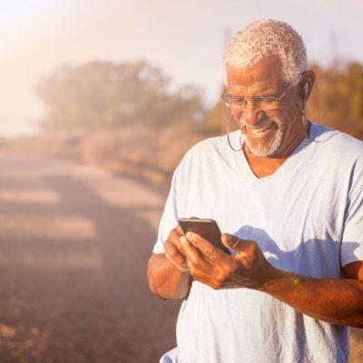 An older man using a cellphone while on a path by a beach