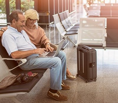 A older couple using a laptop while sitting at an airport