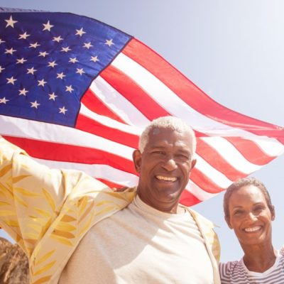 An older couple smiling for the camera while holding an American flag above their heads