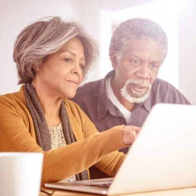 An older couple looking at a laptop while drinking coffee