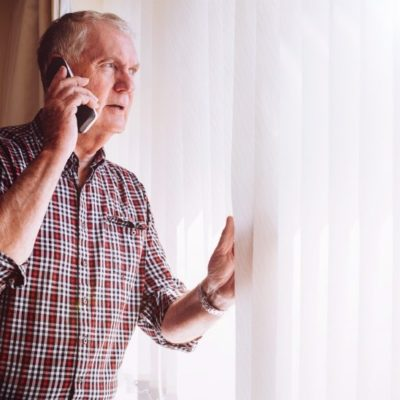 An older man using a cellphone while looking out a window