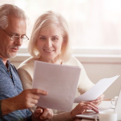 An older couple looking at documents while using a laptop